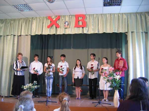 На сцене выпускники и их классный руководитель